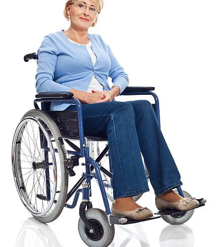 Portrait of mature woman sitting in wheelchair and smiling at camera. Studio shot on white background.